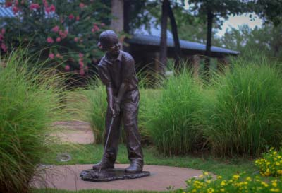 A statue of a child golfing at The Jack Stephens Youth Golf Academy in Little Rock
